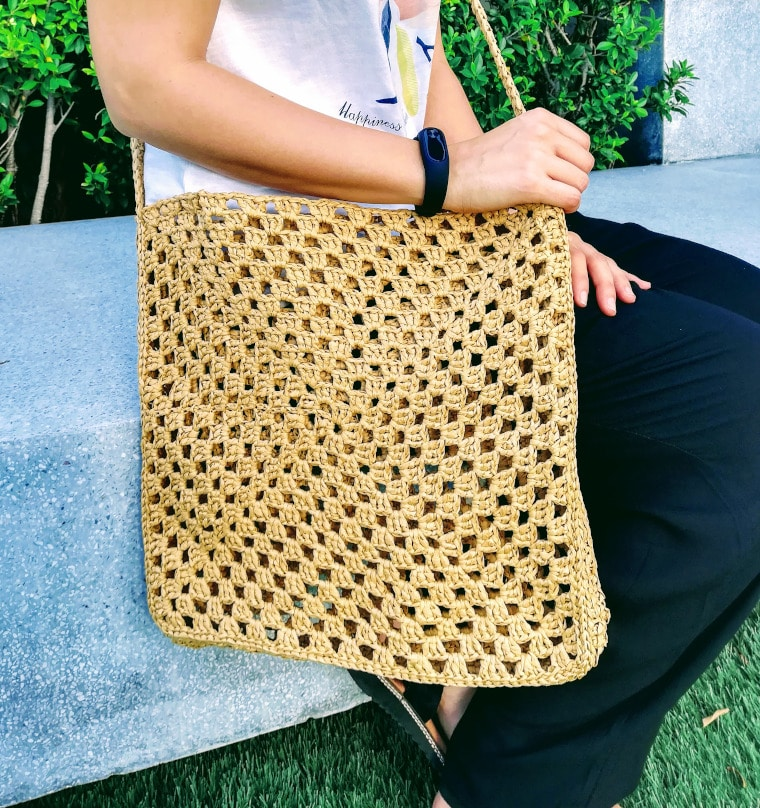 Model holding the Crochet Granny Square Raffia Bag