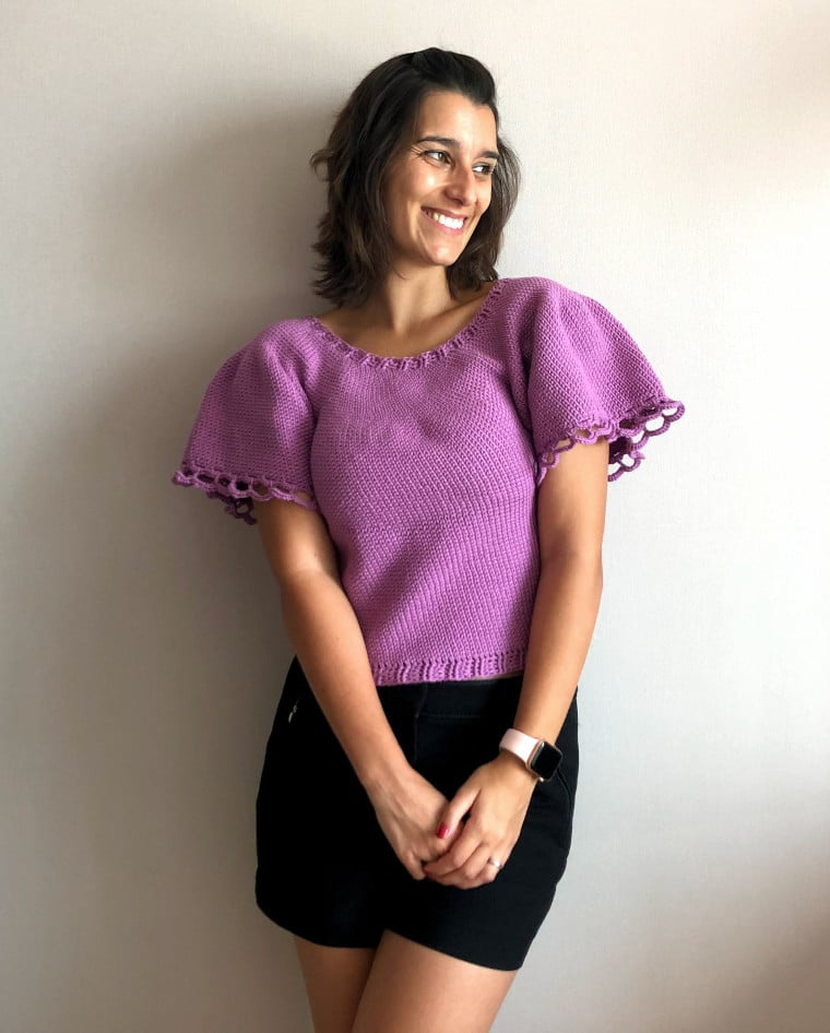 The Crochet Ruffled Romance Sweater designed by Coco Crochet Lee with model wearing a purple sweater