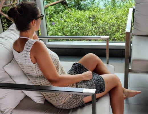Model siting relaxed wearing the Crochet Breezy Beach Dress