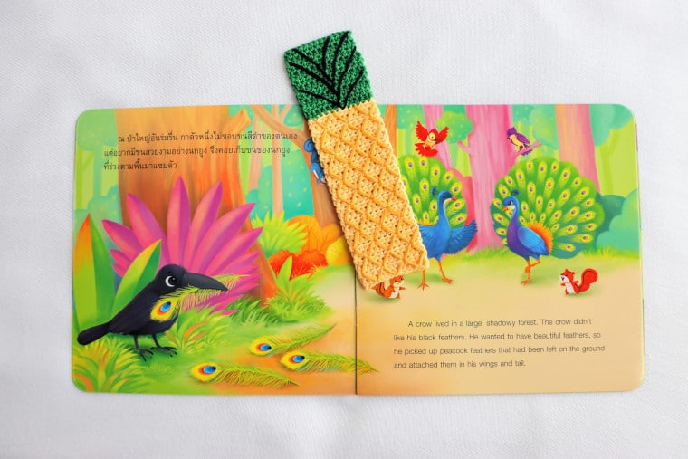 The Pineapple Bookmark of the Crochet Tropical Bookmark Set on a colourful book