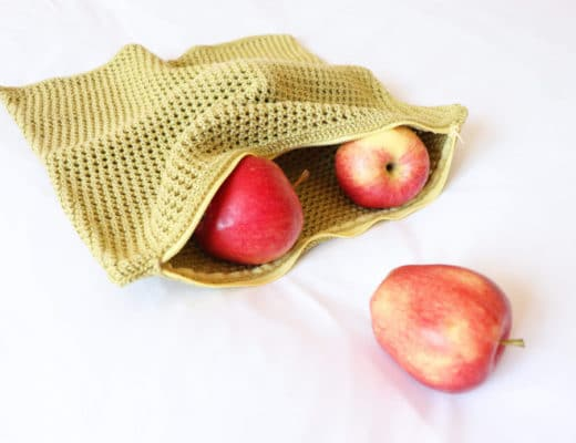 The Crochet Eco-Friendly Fruit & Veggie Bag in green lime with the zipper open showing some apples