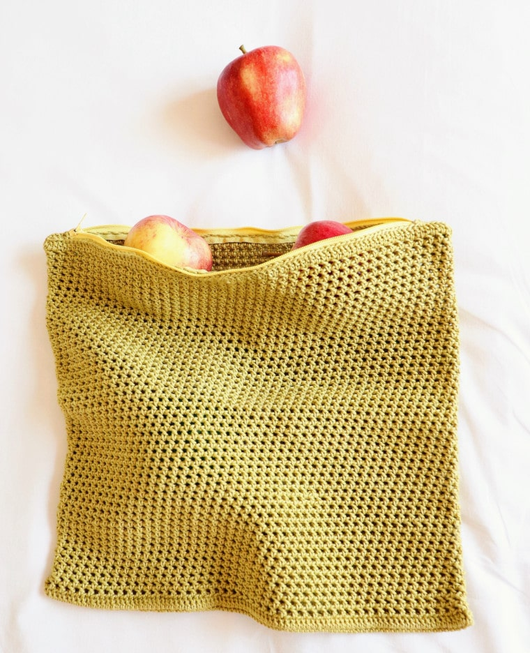 The Crochet Eco-Friendly Fruit & Veggie Bag with apples coming from inside it
