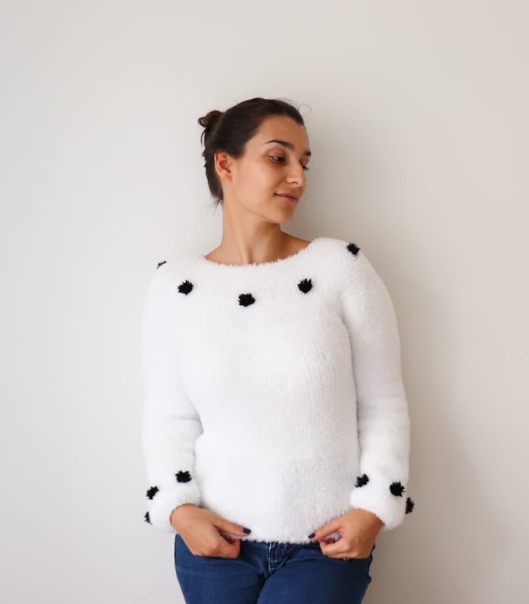 A knit white faux fur sweater pattern with black bobbles seen from the front
