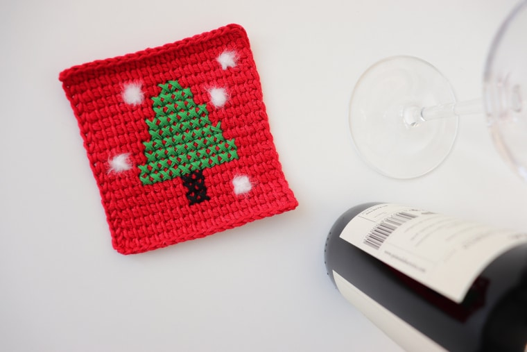 The Tunisian Pine Tree Christmas Coaster on a white table and next to a glass of wine and a small bottle of wine