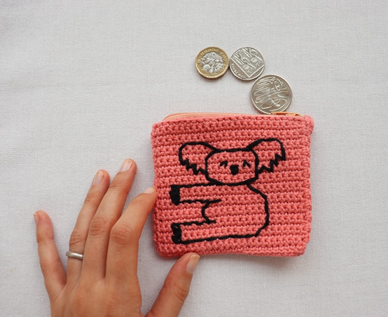 The Crochet Koala Coin Purse laid on a white surface with a hand holding it