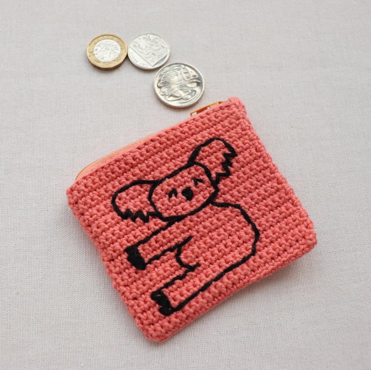 The Crochet Koala Coin Purse laid on a white surface with coin coming out