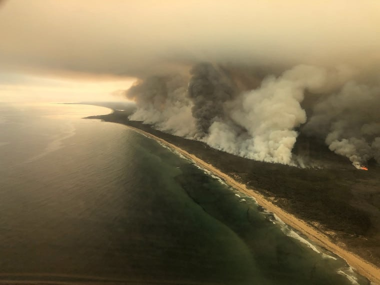 Thick plumes of smoke rise from bush fires on the coast of East Gippsland in Victoria, Australia, on Saturday 4th January 2020
