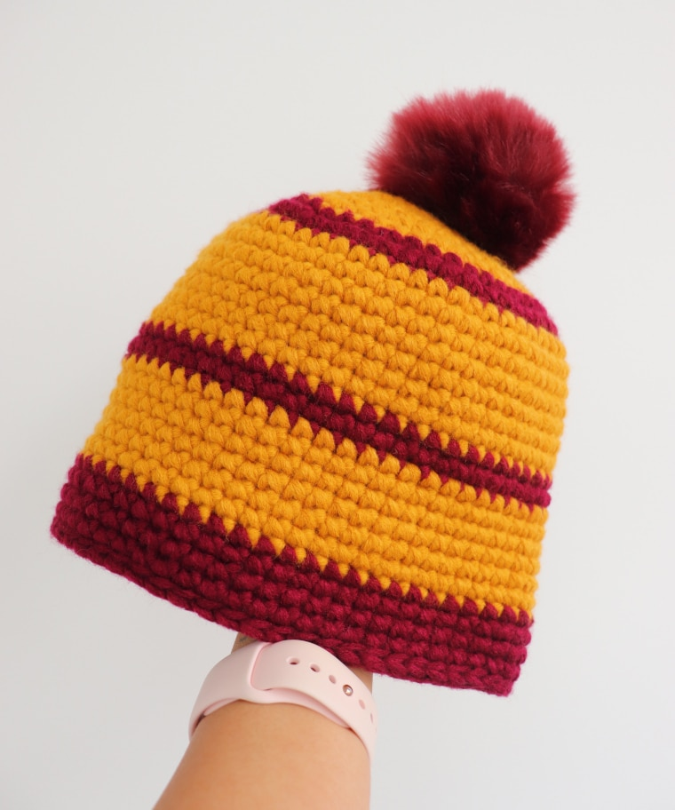 Person with hand inside the Crochet Cross Stitch Beanie against white surface