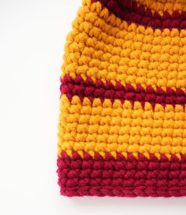 Detail of beanie's brim against white surface