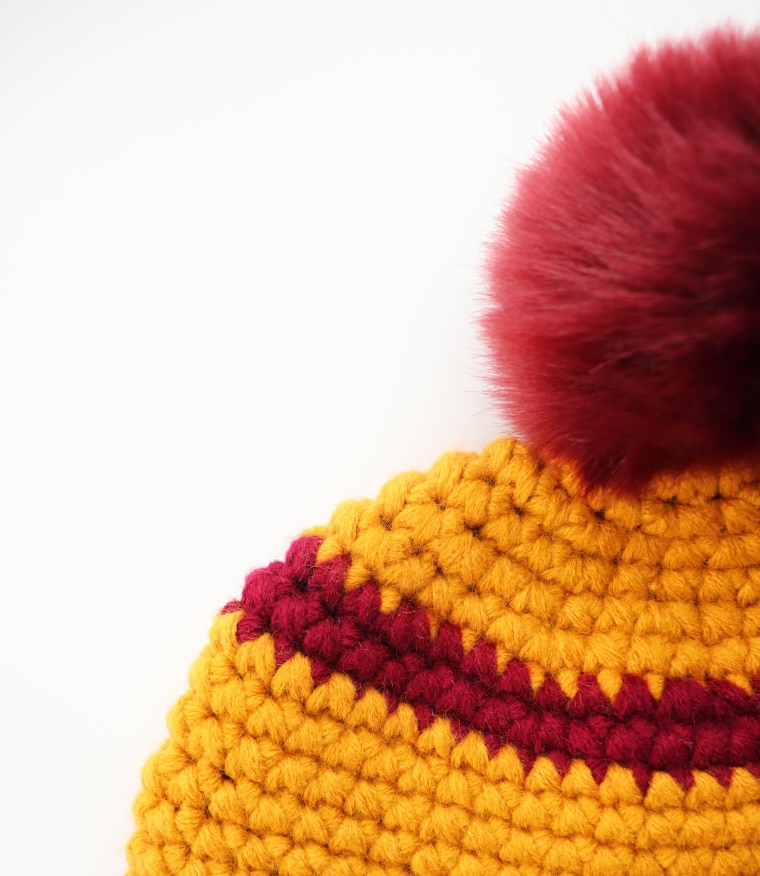 Detail of beanie's crown and Pom Pom against white surface