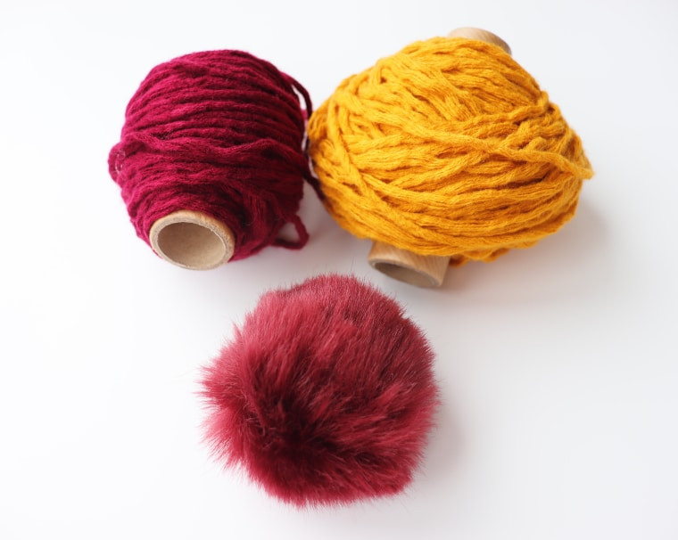 Scraps of purple and mustard yarn and a purple fur Pom Pom against white surface