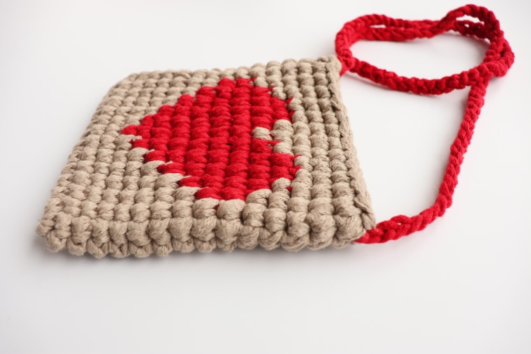 The Lovely Heart Purse seen from the side on a white surface