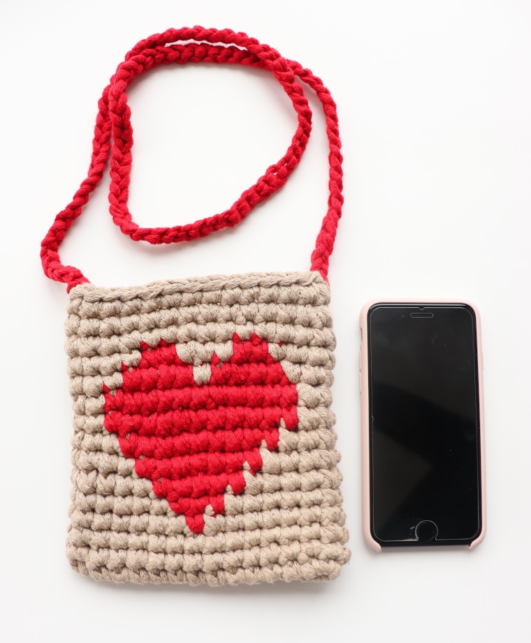 The Lovely Heart Purse with a mobile phone for scale on a white surface