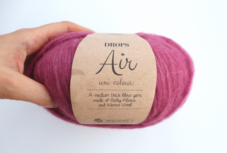 "Person holding a skein of Drops Air yarn in the color ""Heather"" against a white background."