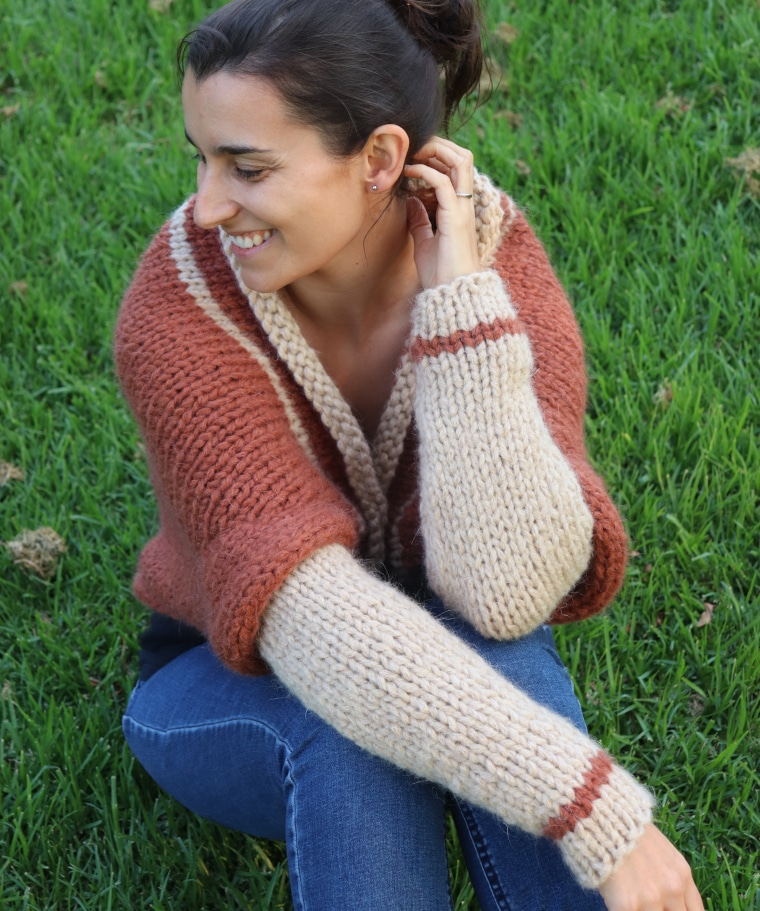 Susana from Fluffy Stitches sitting on the grass wearing the Knit Barcelona Shrug