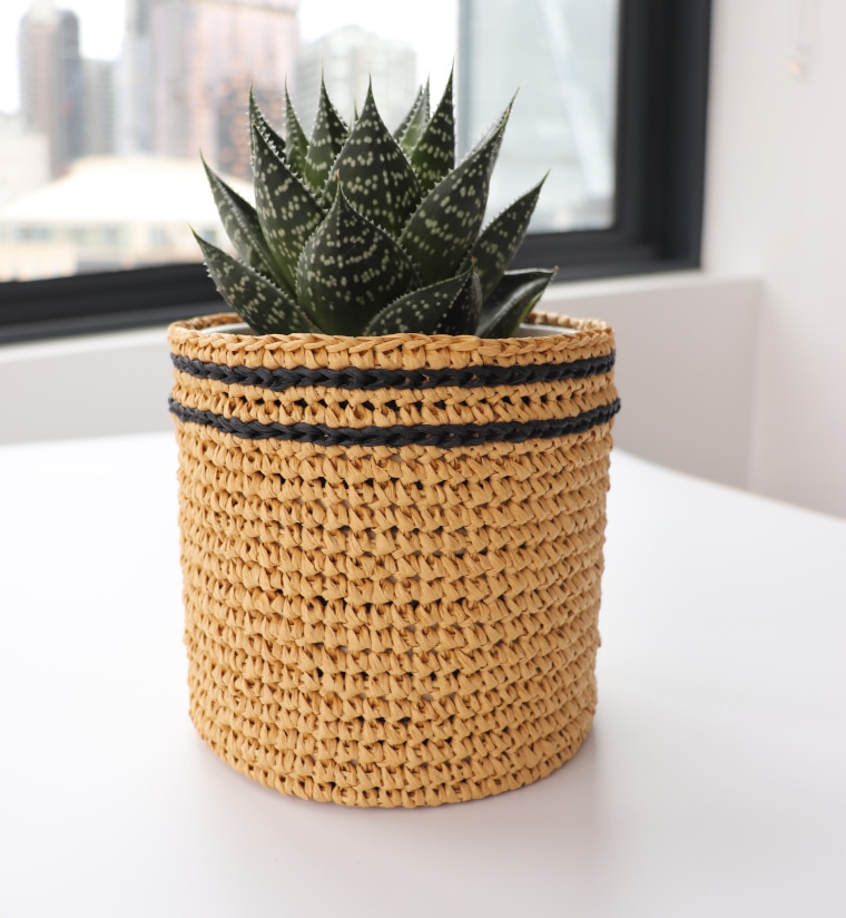 The crochet raffia flower pot sleeve against a cityscape
