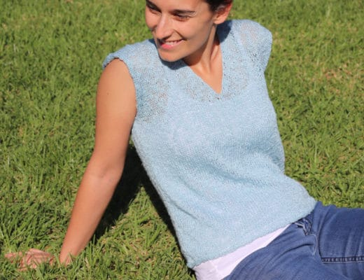 Susana from Fluffy Stitches wearing the Knit Blue Sky Tee sitting on green grass on a summer day