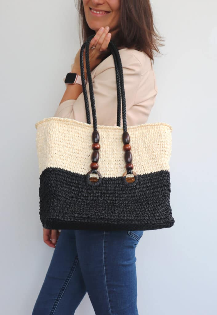 Model holding the raffia bag at shoulder height