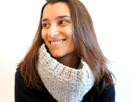 Susana of Fluffy Stitches wearing the Crochet Easy Moss Cowl in light grey and a black sweater against a white background.