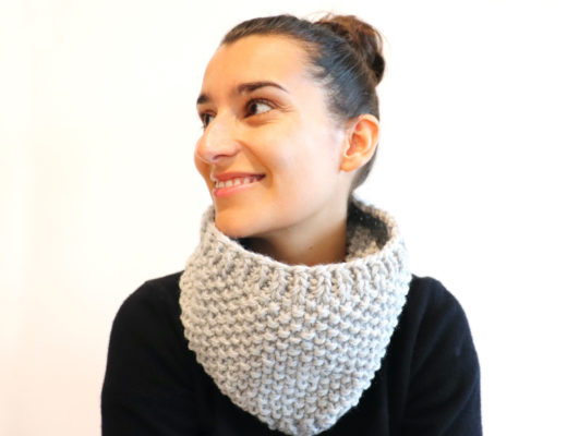 Susana of Fluffy Stitches wearing the Knit Easy Seed Cowl in light grey and a black sweater against a white background.