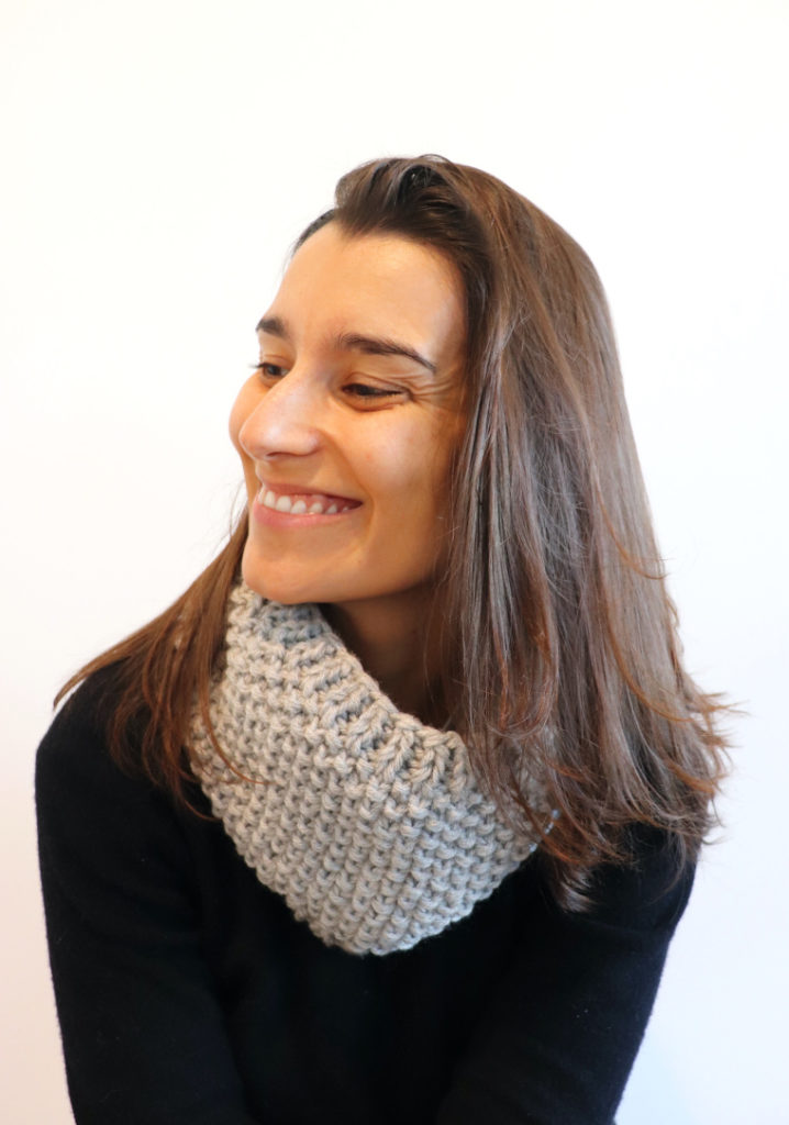 Susana of Fluffy Stitches wearing the Knit Easy Seed Cowl in light grey and a black sweater against a white background
