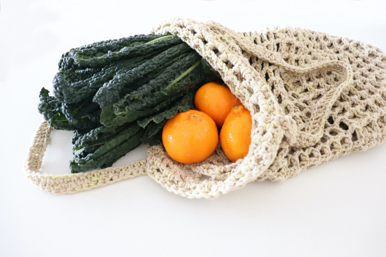 The crochet waffle market bag on a white surface with greens and vegetables coming out