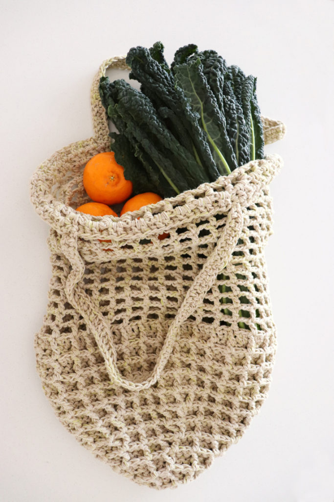 The crochet bag on a white surface with vegetables and fruit inside and coming out