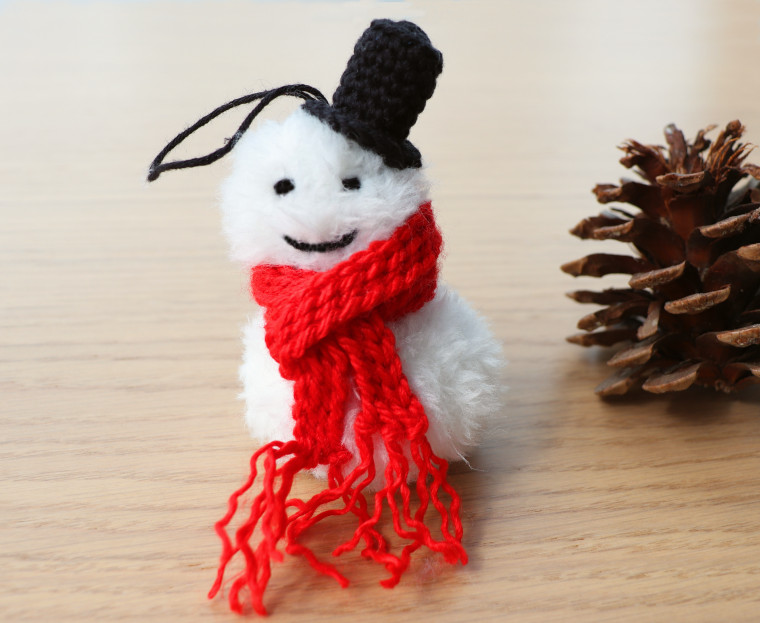 A smiling Crochet Snowman Christmas Ornament, made of white faux fur with a striking red bulky scarf and a black top hat next to a pine cone.