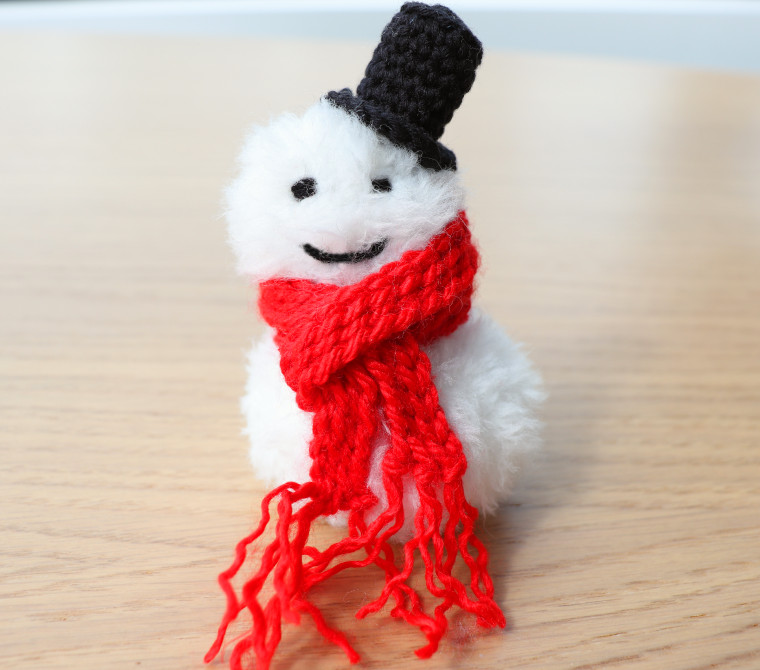 A smiling Crochet Snowman Christmas Ornament, made of white faux fur with a striking red bulky scarf and a black top hat.