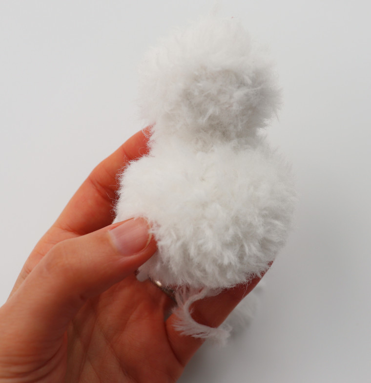 A person holding the two balls of faux-fur that make the body and head of the snowman.