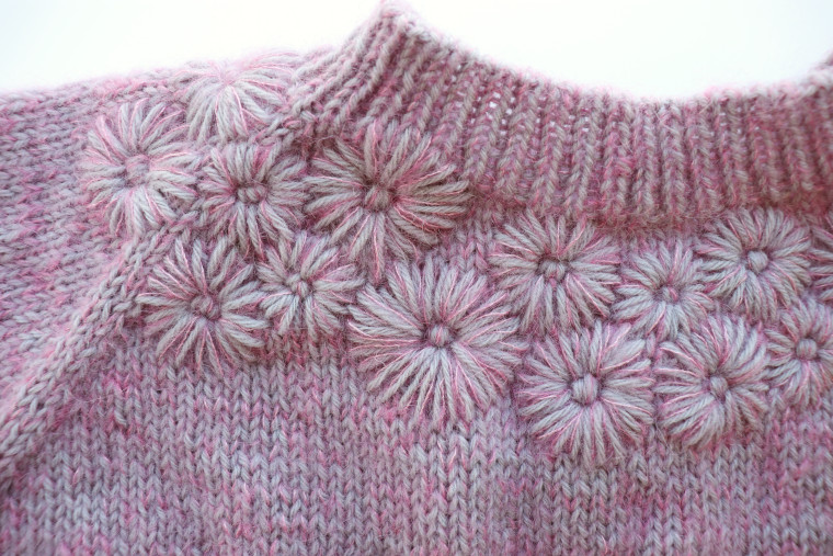 Detail of the embroidered flowers on the yoke of the sweater