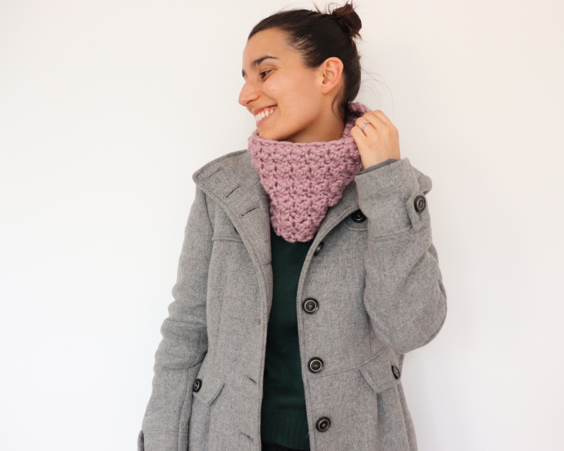 Susana from Fluffy Stitches wearing dusty pink crochet easy textured cowl against a white background
